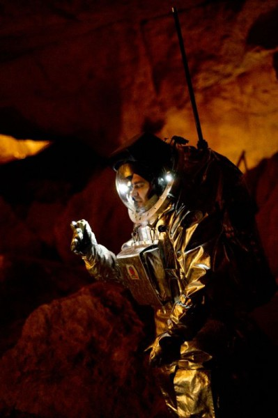 Suit tester Daniel is picking up a stone inside Dachstein cave (c) OEWF (Katja Zanella-Kux)