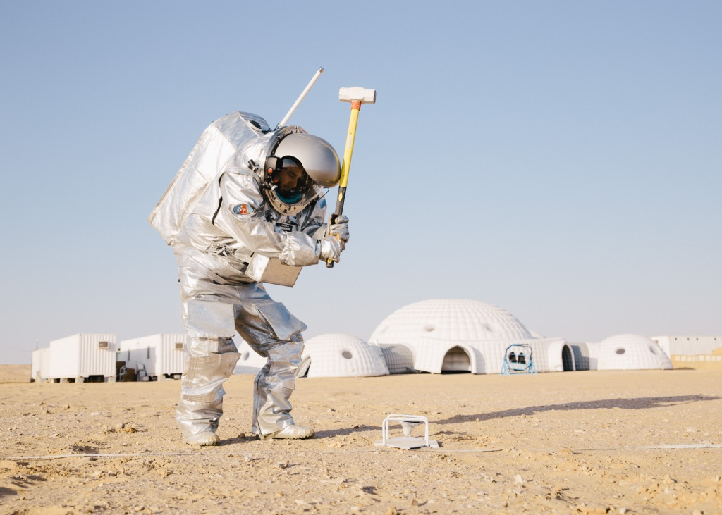 An analog astronaut using a hammer during an experiment. Photo: (c) OeWF (Florian Voggeneder).