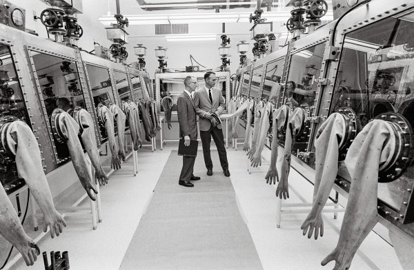 Collins inspiziert die Quarantäne- und Aufbewahrungseinrichtung der NASA am Zentrum für Bemannte Raumfahrt, wo die von den ApolloAstronauten gesammelten Gesteinsproben analysiert wurden. (c) NASA