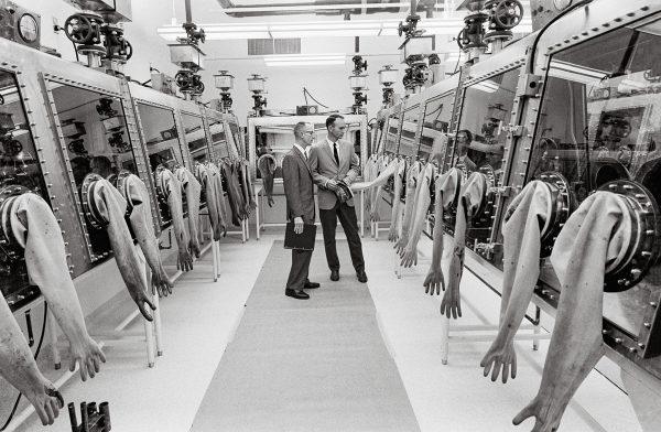 CollinsinspectsNASA'sLunarReceiving LaboratoryatMSC,whererocksamplescollected byApollowereanalyzed. (c) NASA