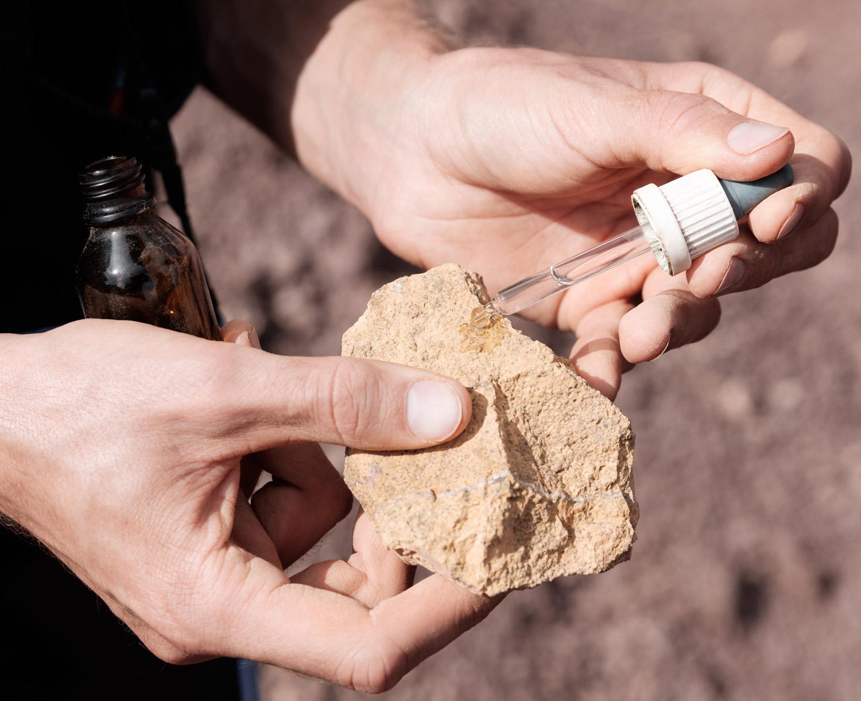 ein Geologe tropft Säure auf ein analog Mars-Gestein, um dieses auf Karbonate zu untersuchen